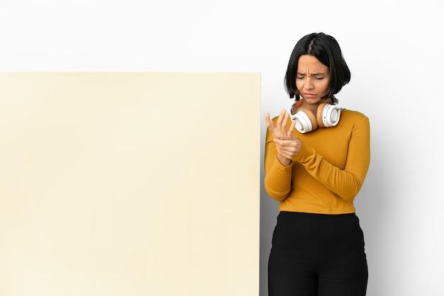 Giovane donna che ascolta musica con un grande cartello vuoto sopra la parete isolata che soffre di dolore alle mani