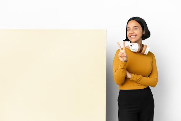 Musica d'ascolto della giovane donna con un grande cartello vuoto isolato