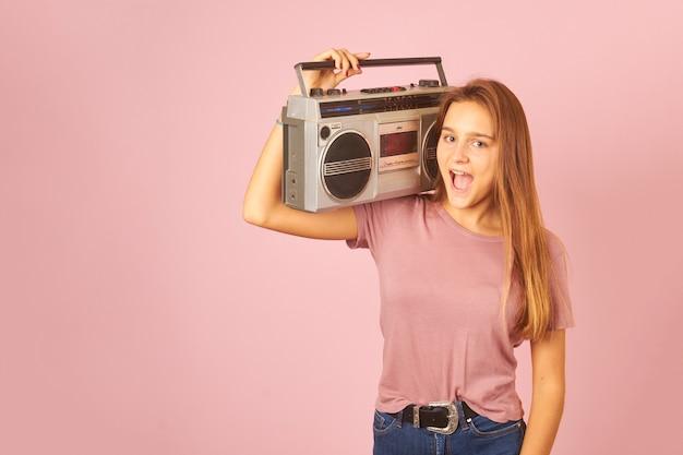 Giovane donna che ascolta la musica con la cassetta della radio d'epoca