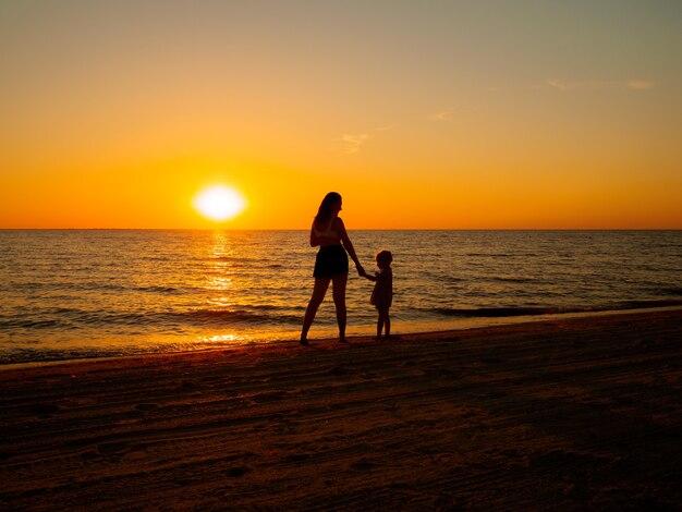 Una giovane donna e una bambina si tengono per mano in riva al mare sullo sfondo del sole al tramonto.