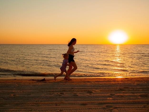 Una giovane donna e una bambina corrono lungo la spiaggia sabbiosa del mare lungo l'acqua. sullo sfondo, il sole della sera tramonta all'orizzonte.