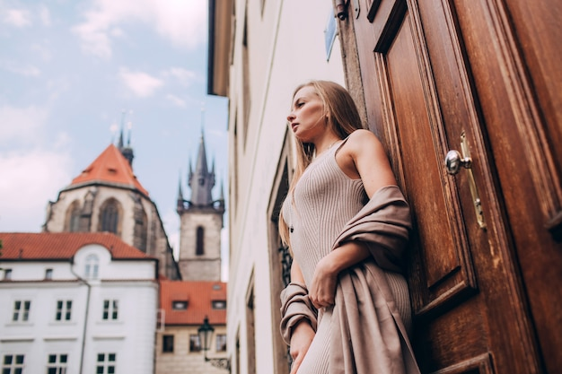 Giovane donna in un lungo abito sulla piazza della città vecchia di praga. giovane turista femminile biondo che gode della grande vacanza nella repubblica ceca.