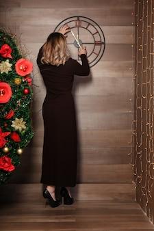 Giovane donna in abito lungo in piedi vicino all'orologio che mostra quasi 12. tempo di impostazione sul muro