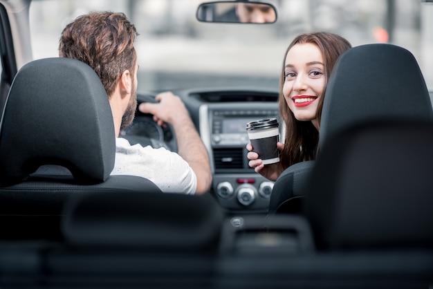 Giovane donna che guarda indietro seduta con un caffè sui sedili anteriori e un uomo alla guida di un'auto