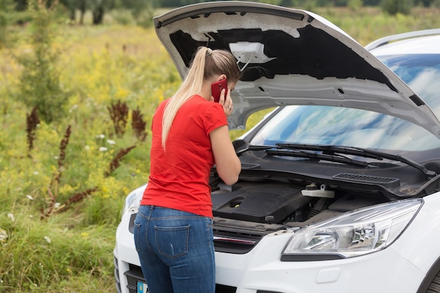 Giovane donna che guarda l'auto rotta e parla al telefono