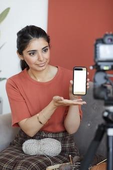 Giovane donna che guarda davanti e indica il suo telefono cellulare condivide la sua vita con i suoi seguaci