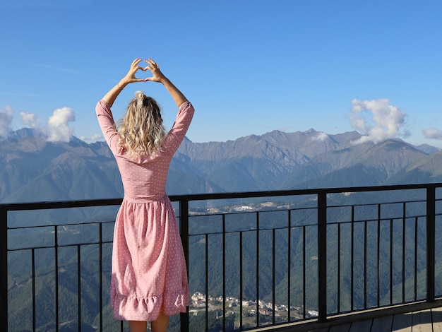 Giovane donna che guarda le montagne e che fa il segno del cuore con le mani