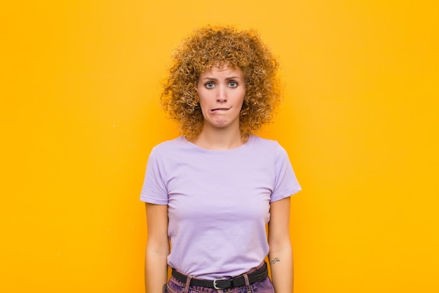 Giovane donna che sembra confusa e confusa, mordendosi il labbro con un gesto nervoso, non conoscendo la risposta al problema sulla parete arancione