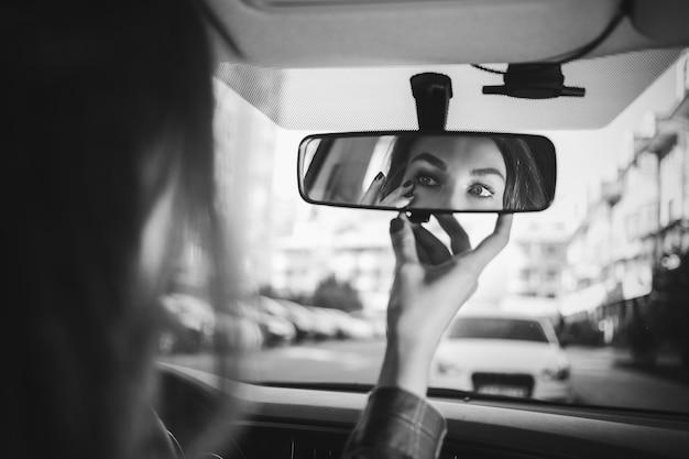 Giovane donna che guarda nello specchietto retrovisore e si trucca in macchina moderna vita frenetica