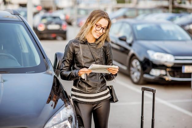 Giovane donna che guarda il contratto di noleggio in piedi all'aperto nel parcheggio dell'aeroporto