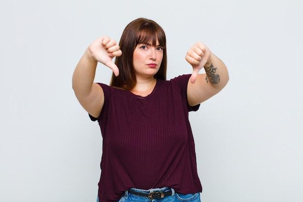 Giovane donna che sembra triste, delusa o arrabbiata, mostra i pollici verso il basso in disaccordo, sentendosi frustrata