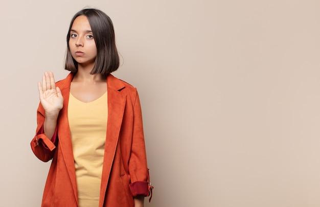 Giovane donna che sembra seria, severa, dispiaciuta e arrabbiata che mostra il palmo aperto che fa il gesto di arresto