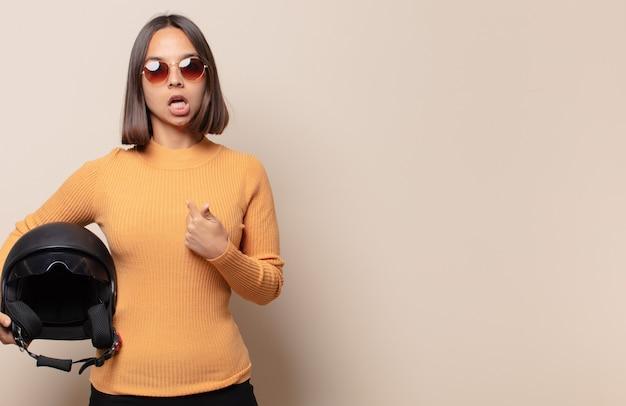 Giovane donna che sembra scioccata e sorpresa con la bocca spalancata, indicando se stessa