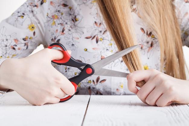 Giovane donna che esamina le doppie punte. capelli lunghi danneggiati