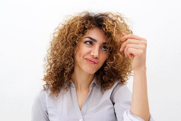 Giovane donna guardando le doppie punte nei capelli