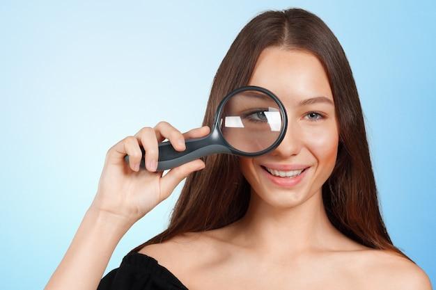 Giovane donna che osserva tramite una lente d'ingrandimento