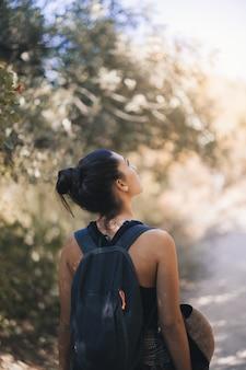 Giovane donna che guarda in alto nella foresta