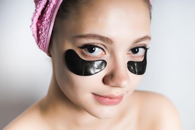 Una giovane donna si prende cura della sua pelle, guarda pensierosa la telecamera, con un asciugamano in testa