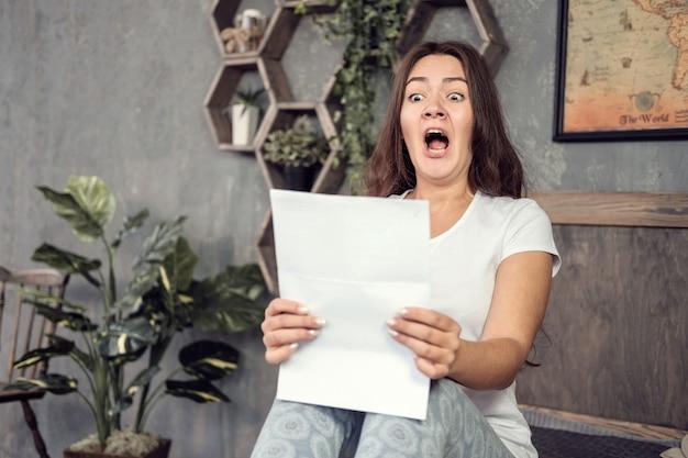 Giovane donna guarda i documenti con sorpresa