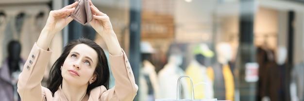 La giovane donna esamina il portafoglio vuoto nel centro commerciale