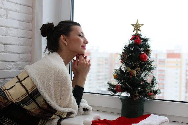 Una giovane donna guarda fuori dalla finestra di un nuovo appartamento