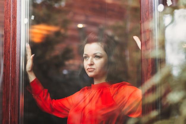 Una giovane donna guarda fuori dalla finestra. considerazioni sull'importante