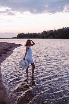 Una giovane donna guarda il tramonto una bella bionda snella felice è in piedi sulla riva del fiume in ...