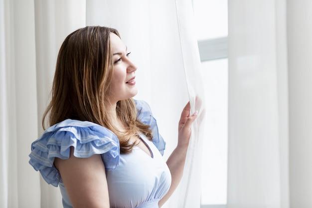 Una giovane donna guarda teneramente fuori dalla finestra. bruna taglie forti. è una bella mattinata. avvicinamento.