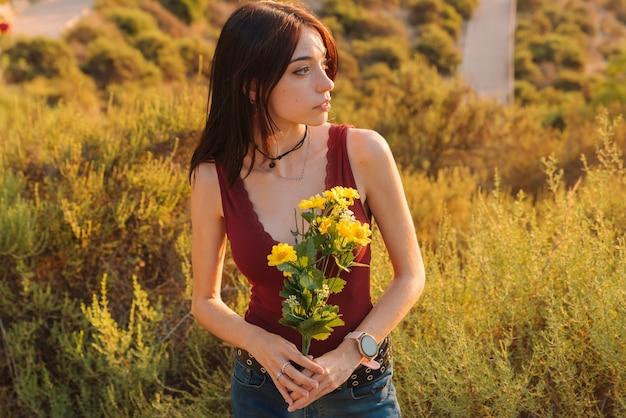 Giovane donna innamorata, con fiori tra le braccia. san valentino