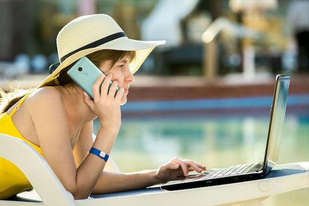Giovane donna sdraiata sulla sedia a sdraio che lavora su un computer portatile connesso a internet wireless