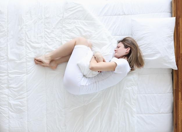 Giovane donna sdraiata a letto e aggrappata a mal di stomaco vista dall'alto. dolorose mestruazioni concetto