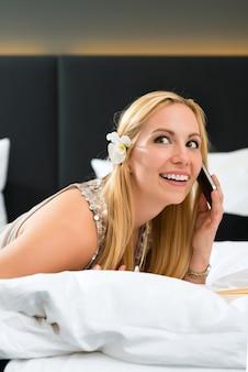 Giovane donna sdraiata nel letto di una camera d'albergo leggendo un libro,