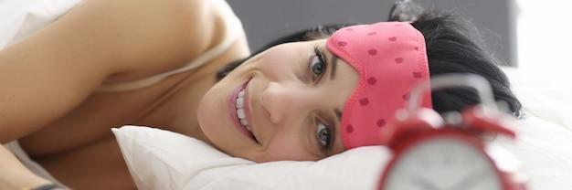 Giovane donna sdraiata a letto che indossa la maschera per dormire. concetto di umore mattutino