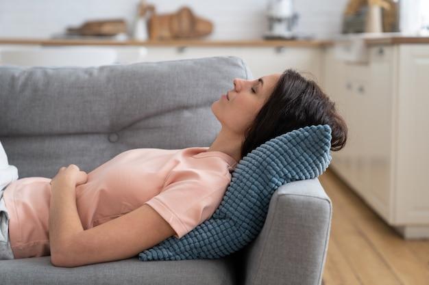 Giovane donna sdraiata sul cuscino sul divano di riposo