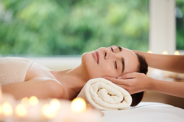 Giovane donna sdraiata e rilassante durante il massaggio termale