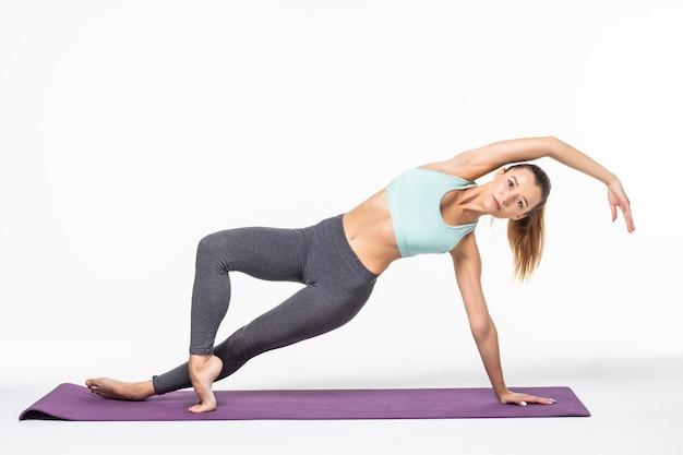 La giovane donna fa esercizi di yoga isolati