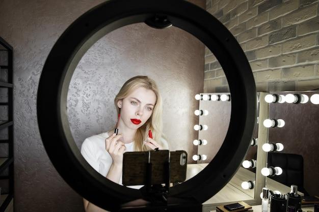 Una giovane donna fa il trucco luminoso con le labbra rosse davanti a uno specchio in uno studio di bellezza