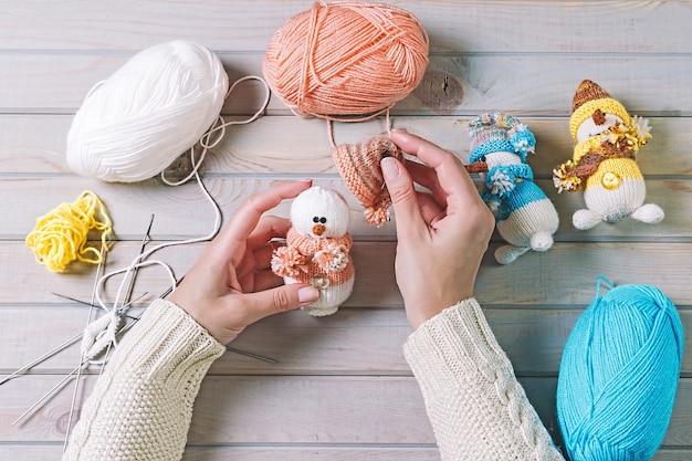 Giovane donna che fa i giocattoli fatti a mano di natale sulla tavola di legno