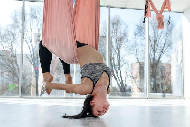 Giovane donna che fa esercizi di yoga volante
