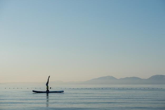 Giovane donna che fa la testa stare su una tavola di sup che galleggia sulle acque calme dell'oceano di mattina.