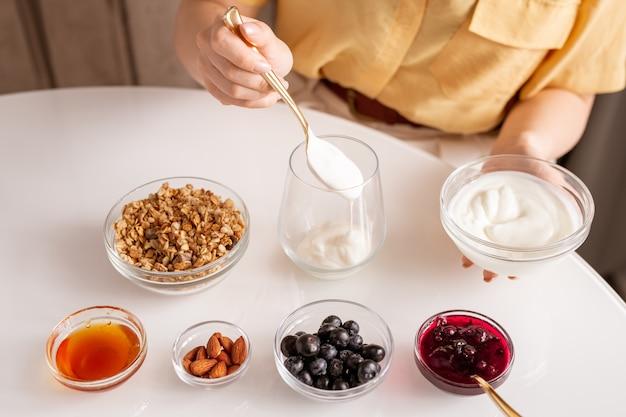 Giovane donna che fa yogurt fatto in casa con panna acida, muesli, miele, noci di mandorle, more fresche e marmellata di ciliegie per colazione