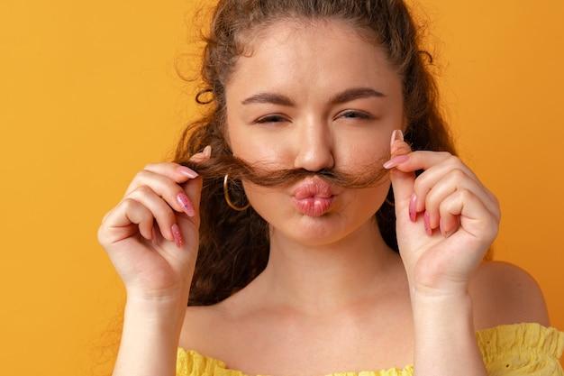 Giovane donna che fa i baffi con i suoi capelli su sfondo giallo
