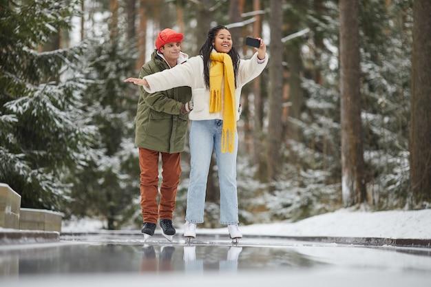 Giovane donna che fa selfie ritratto sul cellulare mentre pattina insieme al suo fidanzato all'aperto in inverno