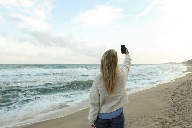 Giovane donna che fa selfie sulla spiaggia di sabbia del mare