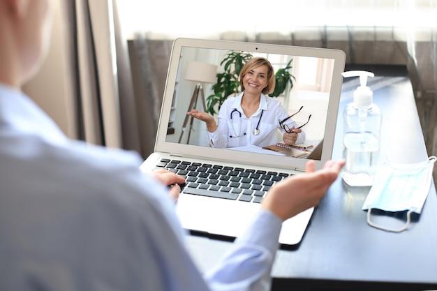 Giovane donna che effettua una videochiamata con il suo medico durante l'autoisolamento e la quarantena