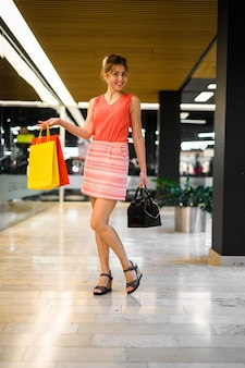 Giovane donna in un centro commerciale, a figura intera