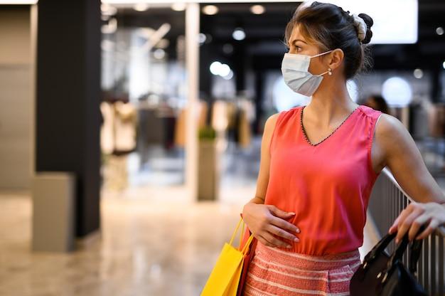 Giovane donna in un centro commerciale che indossa una maschera protettiva contro la pandemia di coronavirus covid 19