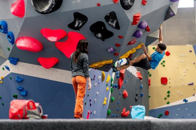 Una giovane donna e un uomo arrampicata su parete di arrampicata praticando arrampicata su roccia.