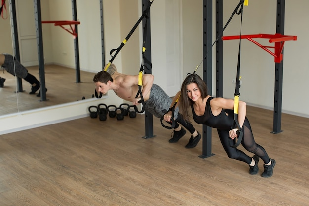 Esercizio di allenamento di giovane donna e uomo push up con cinghie di fitness trx in palestra concetto di allenamento sportivo stile di vita sano.