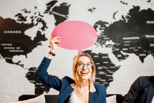 Giovane donna manager che sogna con una bolla colorata sopra la testa seduta in ufficio con una mappa del mondo sullo sfondo
